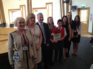 Pupils and staff from St Blanes PS, Blantyre receive their 'Champions for Change ' award from Yvonne Donald (NBM) and James Kelly MSP at the Scottish Parliament
