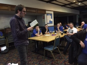 Players and officials from Mauchline Utd ponder the quiz round on ' Gaffers'